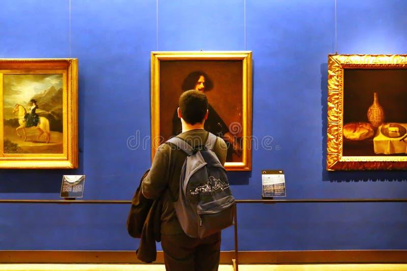 Ung man observera en bild i det Uffizi museet arkivfoto
