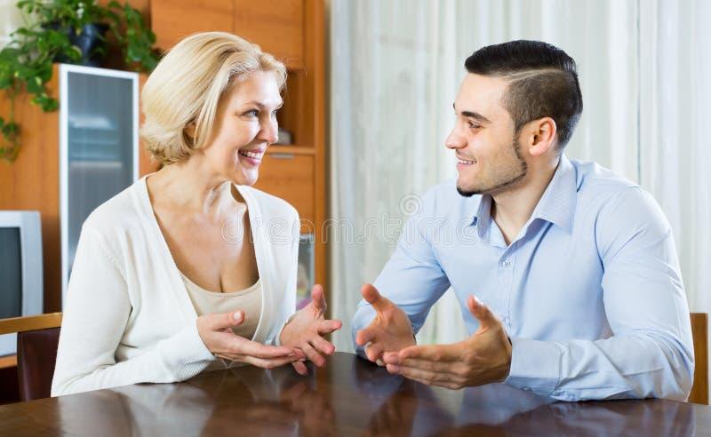 Ung man och åldrig kvinna som inomhus talar arkivbild