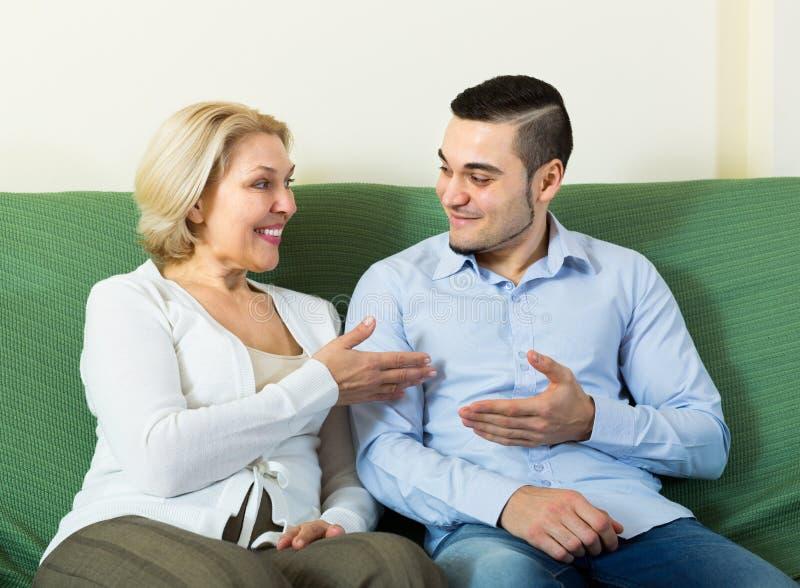 Ung man och åldrig kvinna som inomhus talar royaltyfri foto