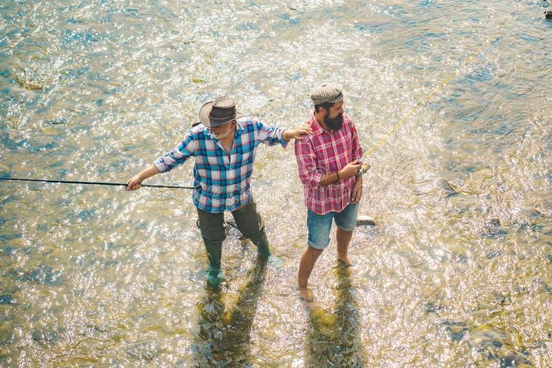 Ung man och gammalt moget manflugafiske Farfar och pojke som tillsammans fiskar Flyga stången och rullen med en brun forell från arkivbild