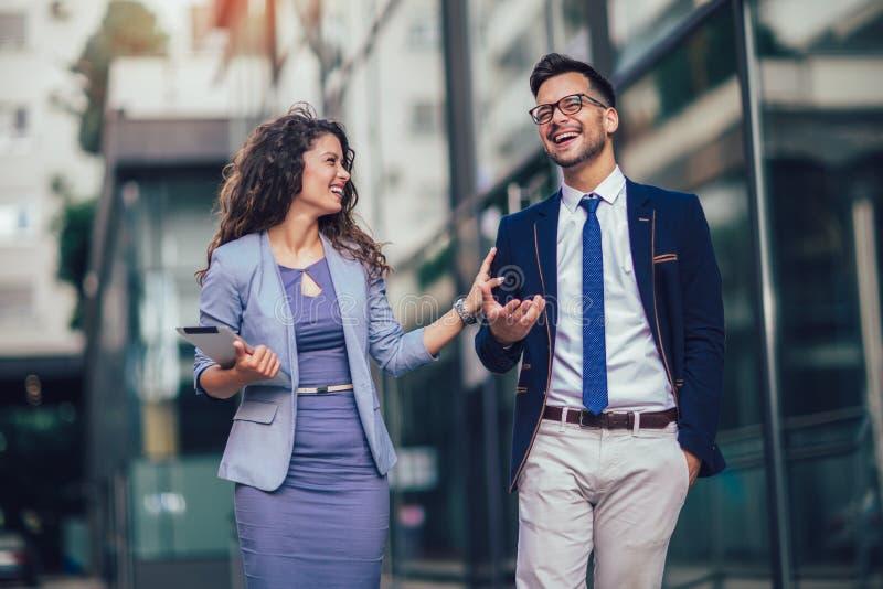 Ung man och härlig kvinna som affärspartners som använder den utomhus- digitala minnestavlan royaltyfri foto