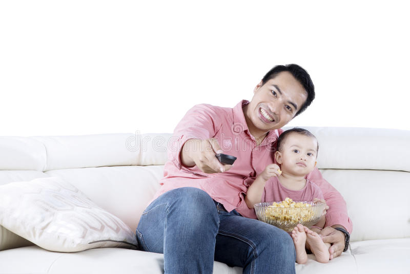 Ung man och hållande ögonen på TV för dotter royaltyfria foton