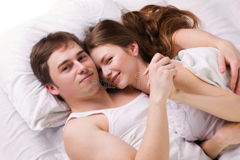 Ung man och kvinna i en säng arkivfoto