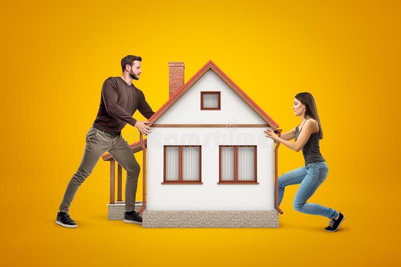 Ung man och kvinna i tillfällig kläder som rymmer ett stort vitt hus med det röda taket på gul bakgrund royaltyfria bilder
