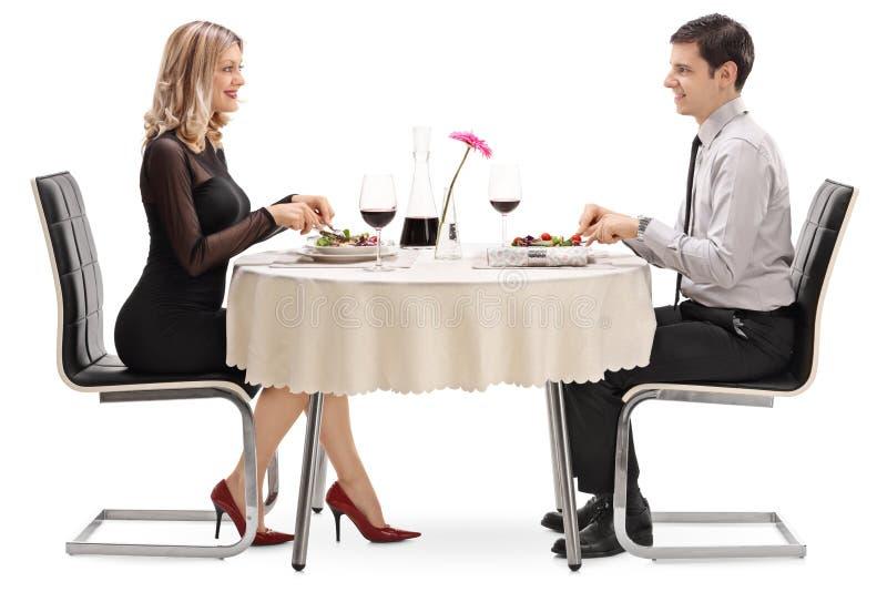 Ung man och kvinna som äter på ett datum arkivfoto