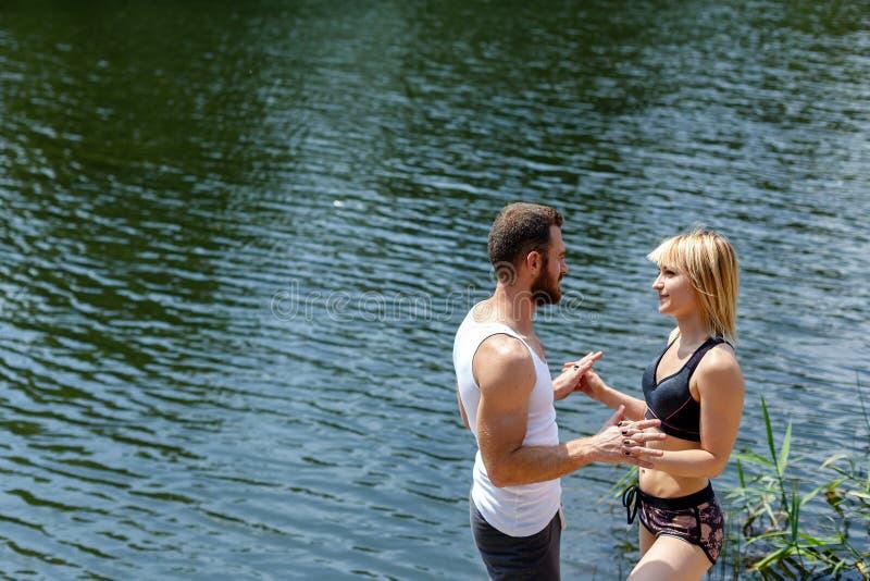 Ung man och kvinna som går i parkera nära floden royaltyfri fotografi