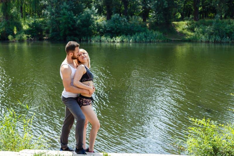 Ung man och kvinna som kramar och att gå i en parkera nära floden arkivbilder