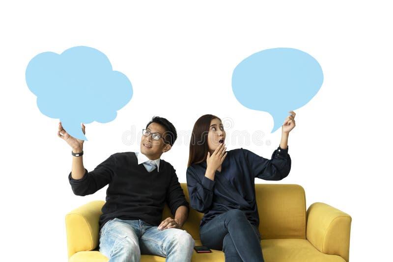 Ung man och kvinna som sitter på soffan som rymmer en anförandebubbla på vit bakgrund fotografering för bildbyråer
