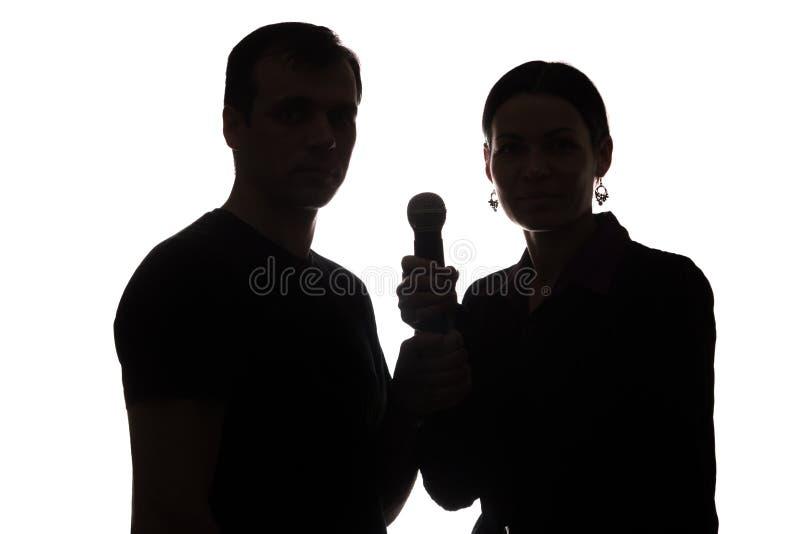Ung man och kvinna som sjunger in i mikrofonen royaltyfria foton