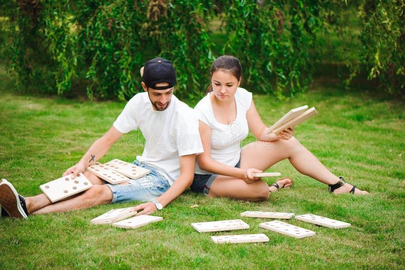Ung man och kvinna som spelar jätte- domino i parkera på gräset royaltyfri fotografi
