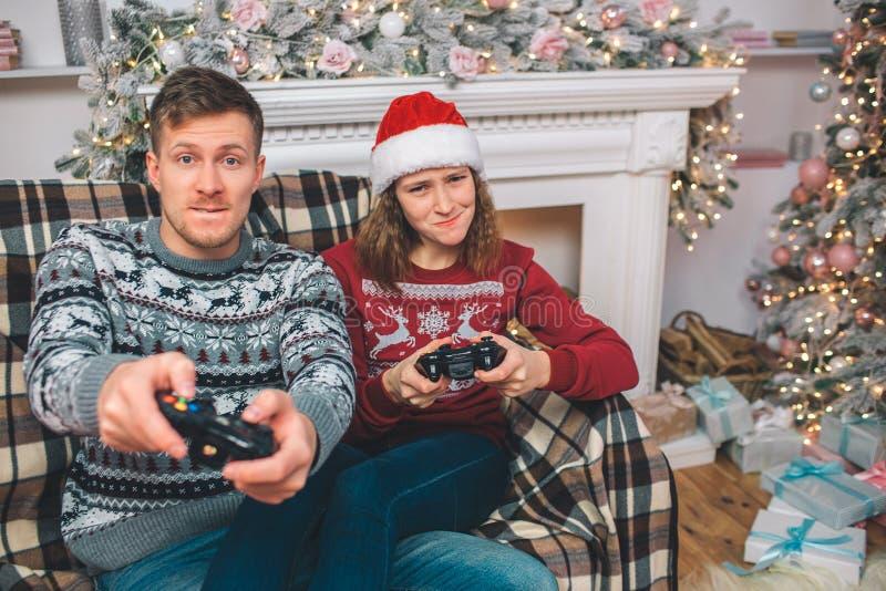 Ung man och kvinna som tillsammans sitter och spelar lekar Dem tryckknappar på konsolen Folkbekymmer De spelar in fotografering för bildbyråer