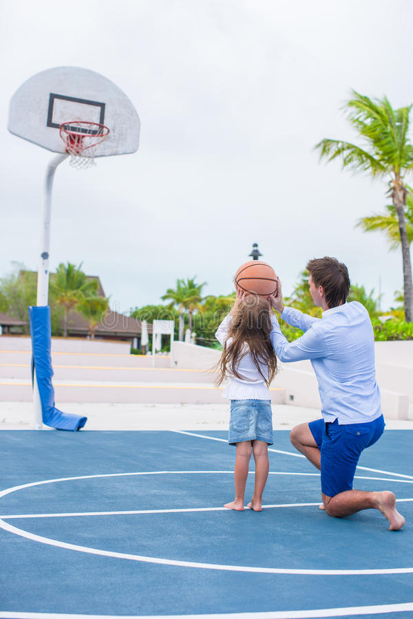 Ung man och liten flicka som spelar basket arkivfoto