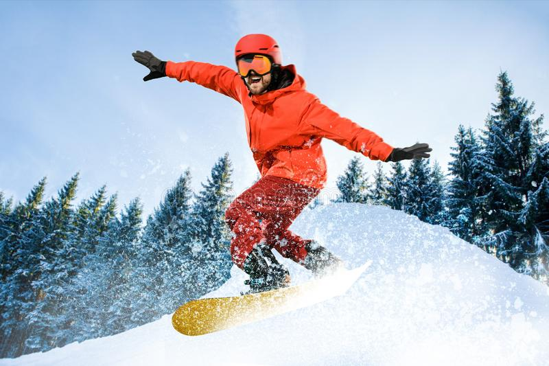 Ung man och vintersport som skidar mot vita fjällängberg royaltyfri bild