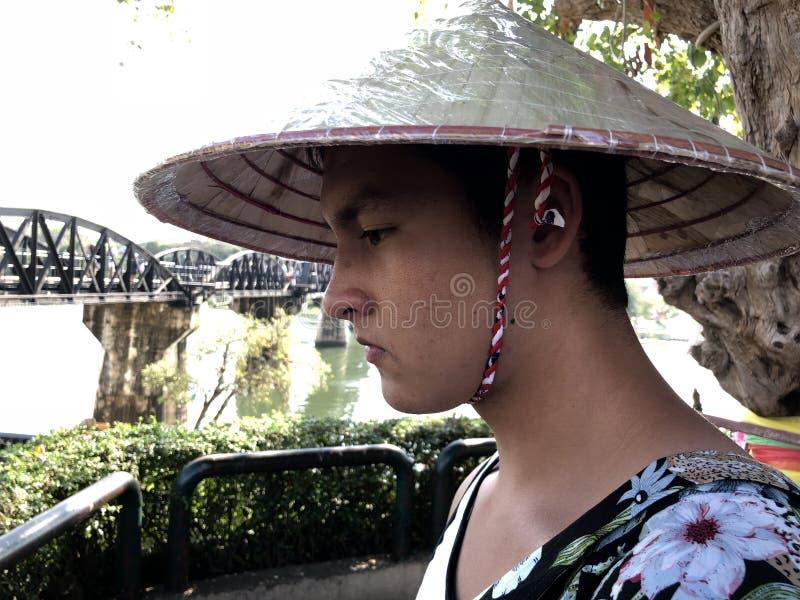 Ung man på bron på floden Kwai royaltyfria foton