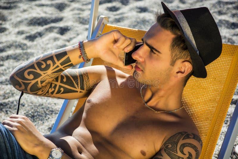Ung man på deckchair på stranden som talar på telefonen arkivbild