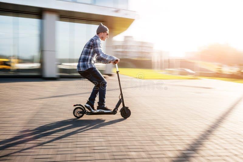 Ung man på den elektriska sparkcykeln på gatan arkivfoto