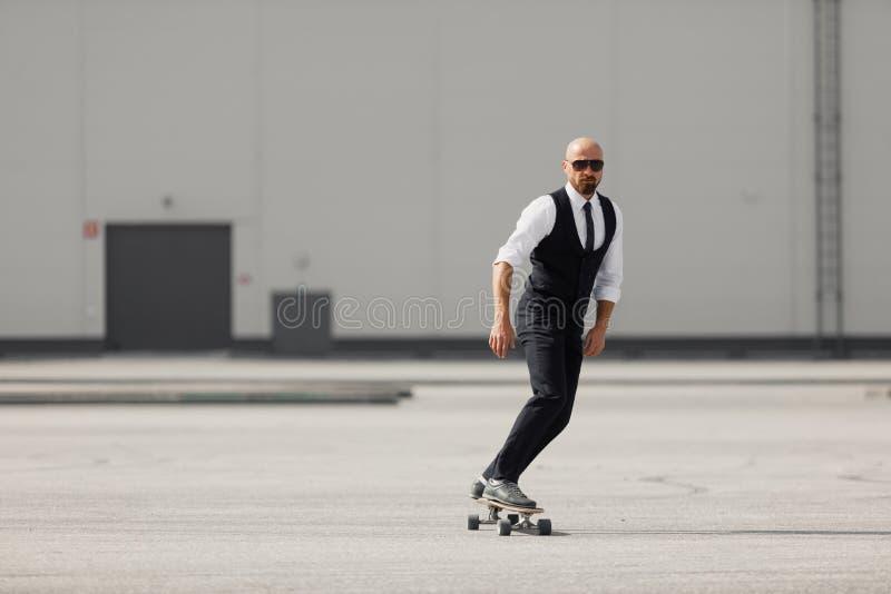 Ung man på den trevliga dräkten för mode på longboardskatebourden på flygplatsen nära modern byggnad royaltyfria foton