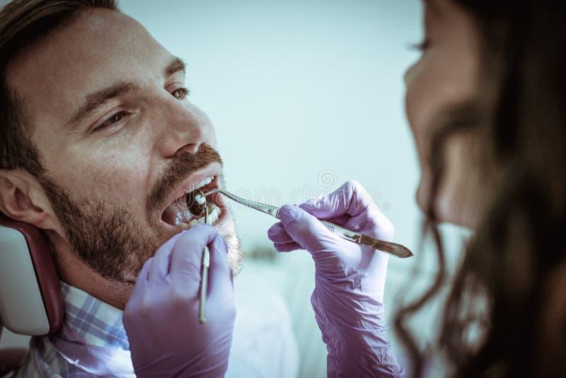 Ung man på det kvinnliga tandläkarekontoret royaltyfri bild