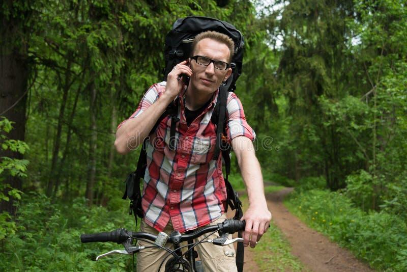 Ung man på en cykel som talar i skogen på en mobiltelefon fotografering för bildbyråer