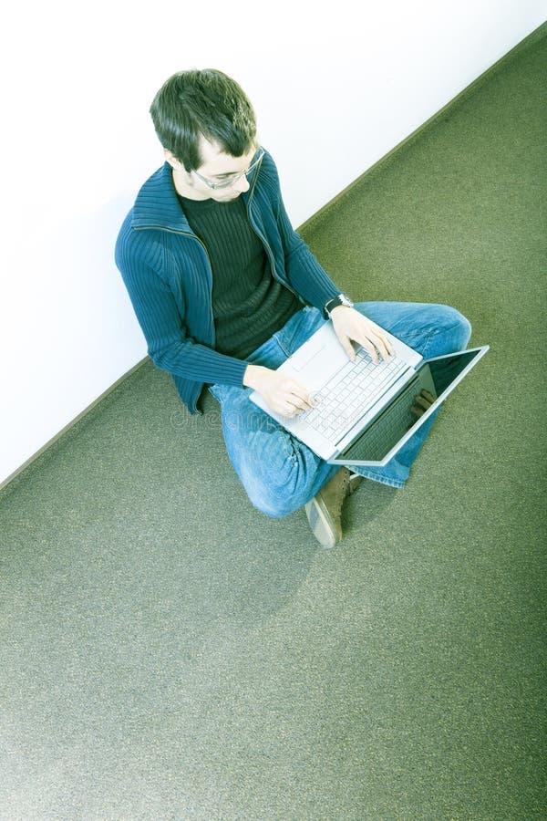 Ung man på golv med bärbar dator royaltyfria bilder