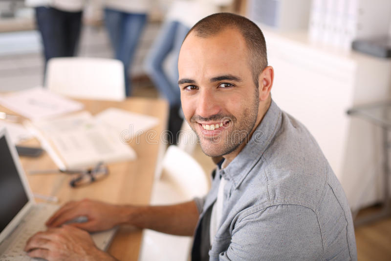 Ung man på kontoret som arbetar på leptop arkivbilder