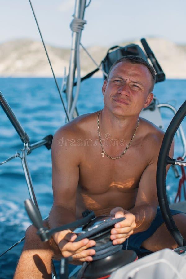 Ung man på rodern av en seglingyacht hobby arkivbilder