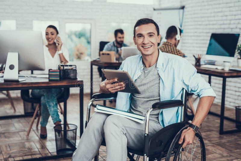 Ung man på rullstolen med minnestavlaPC i regeringsställning royaltyfria bilder