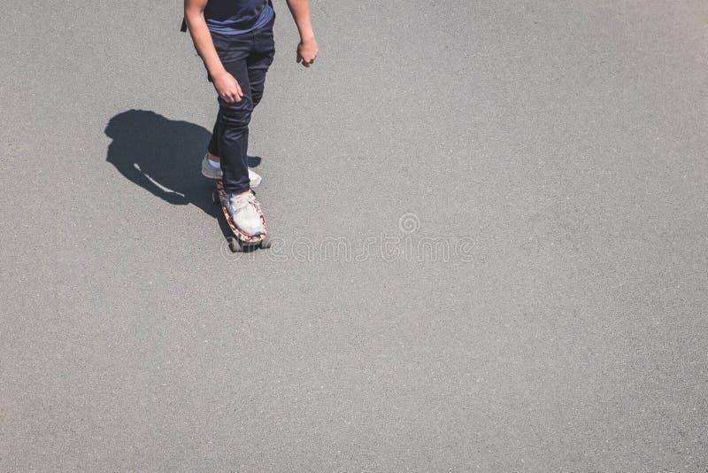 Ung man på skateboarden på asfaltvägen med kopieringsutrymme från abo arkivbild