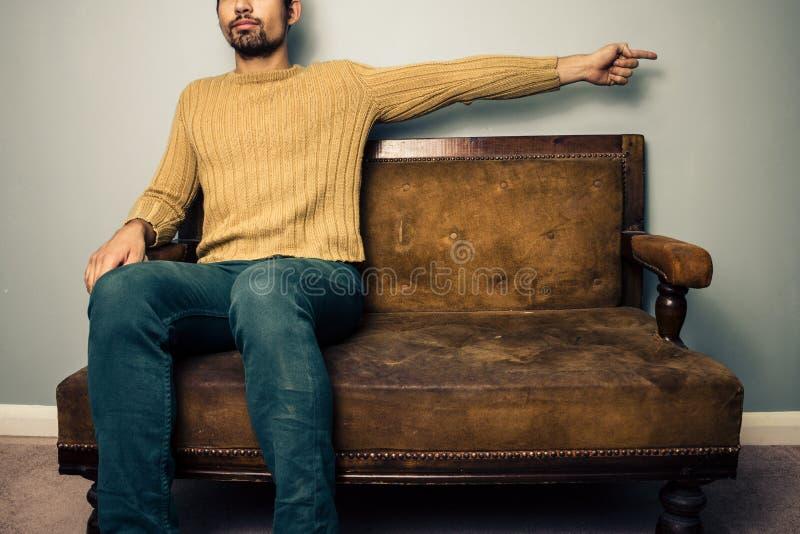 Ung man på soffan som rätt pekar royaltyfri fotografi