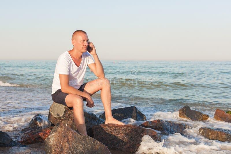 Ung man på stranden med en telefon arkivfoto