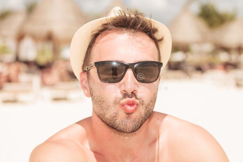 Ung man på stranden som överför dig en kyss royaltyfria bilder