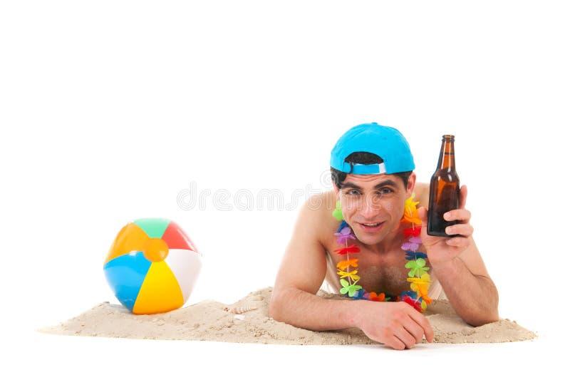 Ung man på stranden som dricker öl arkivfoto
