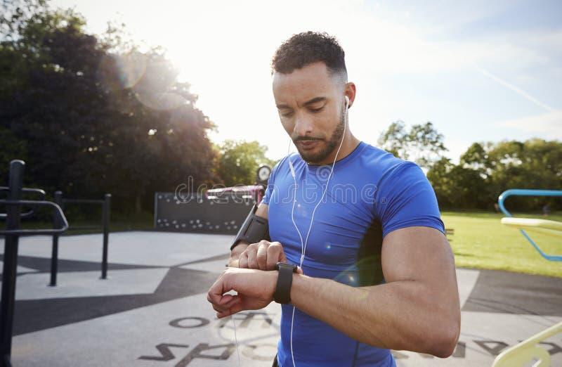 Ung man på utomhus- idrottshallinställningskondition app på smartwatch arkivfoton