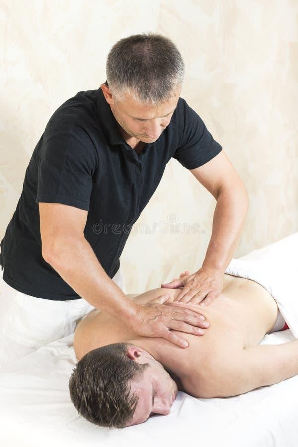 Ung man p? wellnessbehandlingmassage royaltyfria bilder
