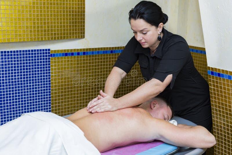 Ung man p? wellnessbehandlingmassage arkivfoto