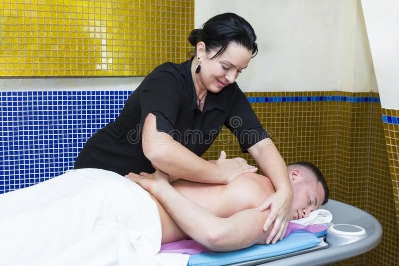 Ung man p? wellnessbehandlingmassage royaltyfria foton