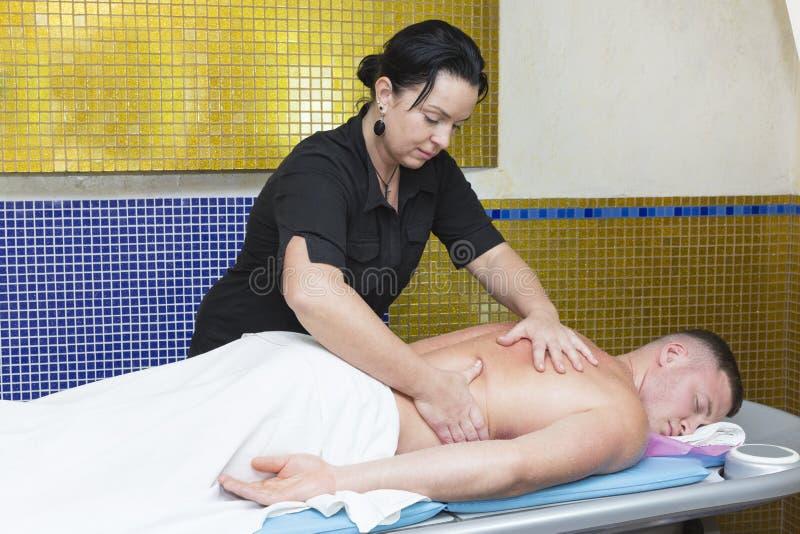 Ung man p? wellnessbehandlingmassage arkivbild