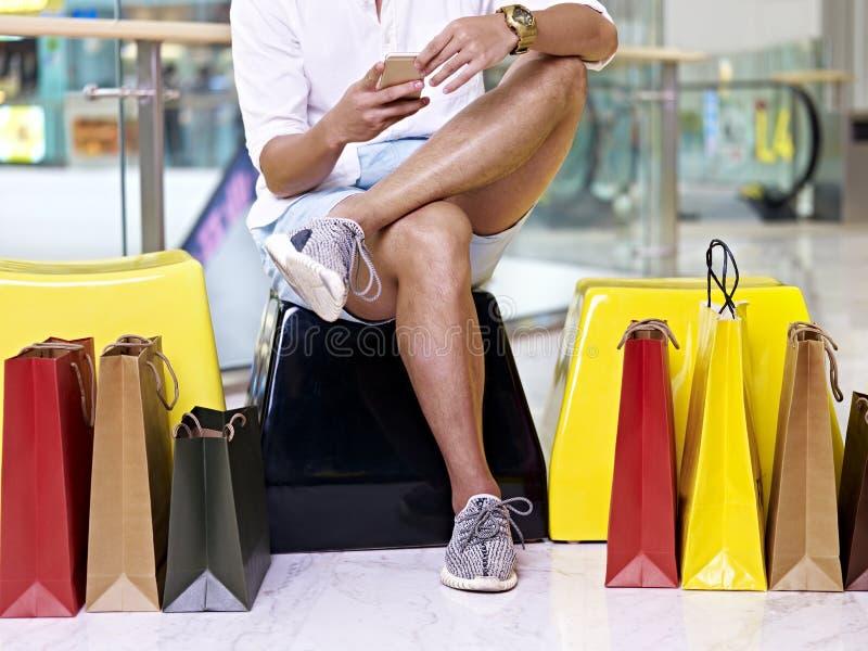 Ung man& x27; s-ben och färgrika shoppingpåsar royaltyfri bild