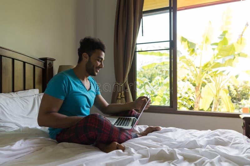 Ung man Sit On Bed, lycklig leendelatinamerikan Guy Bedroom Using Laptop Computer royaltyfri foto