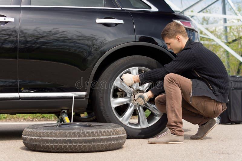 Ung man som ändrar det punkterade däcket på hans bil royaltyfri fotografi