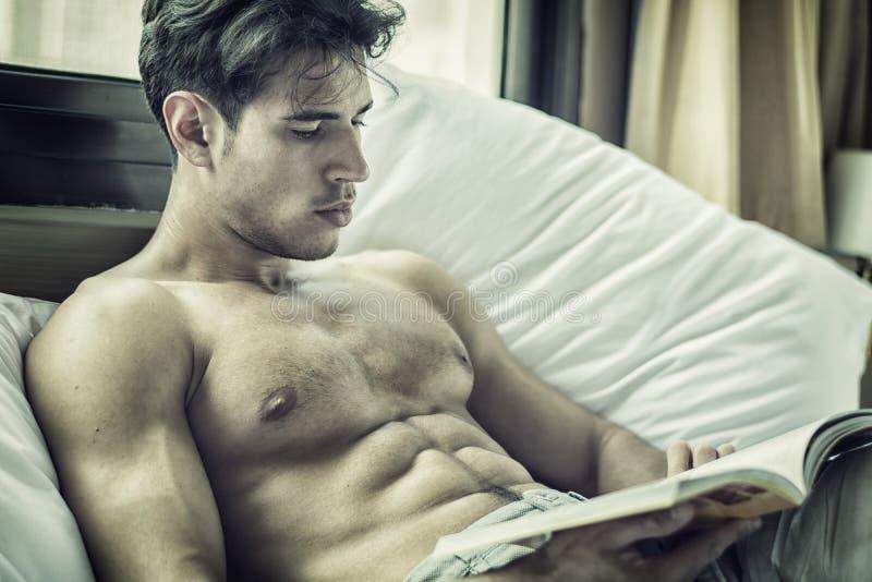 Ung man som är shirtless på hans säng som läser en bok royaltyfri fotografi