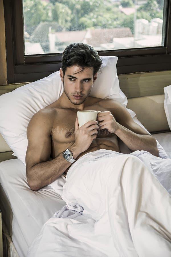 Ung man som är shirtless på hans säng med en kaffe- eller tekopp arkivfoto