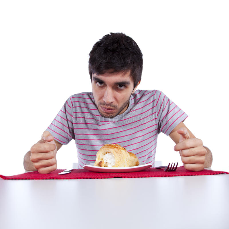 Ung man som äter en cake arkivbilder