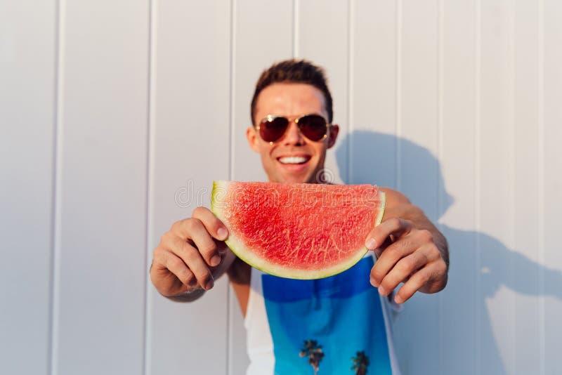 Ung man som äter en vattenmelon, utomhus royaltyfria foton