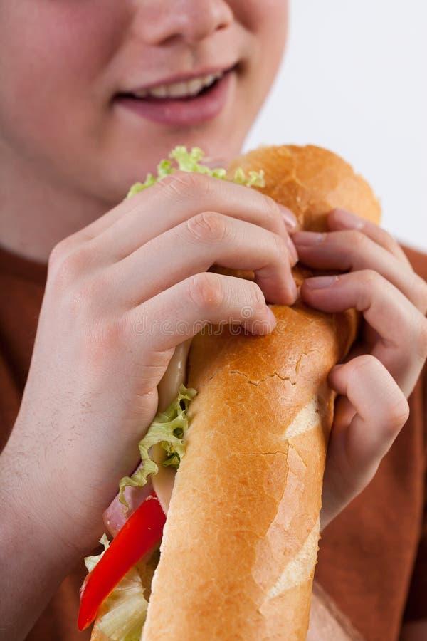 Ung man som äter smörgåsen royaltyfri bild