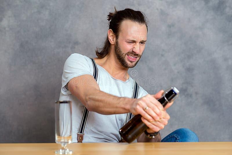 Ung man som öppnar en ölflaska fotografering för bildbyråer