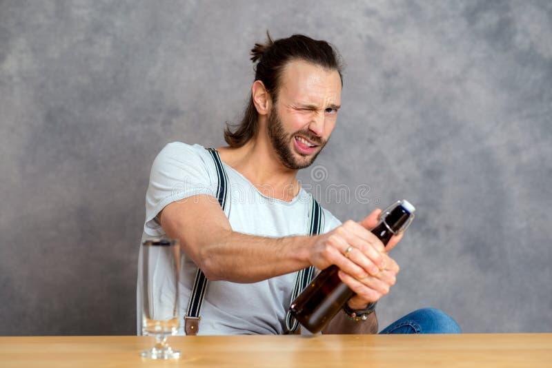 Ung man som öppnar en ölflaska arkivfoton
