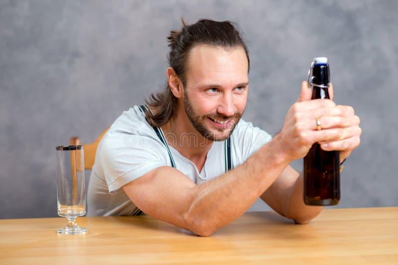 Ung man som öppnar en ölflaska royaltyfri foto