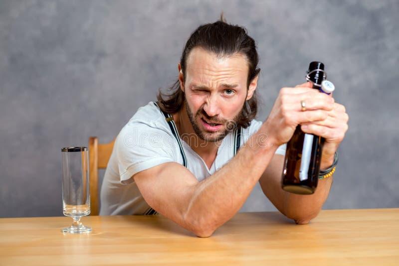 Ung man som öppnar en ölflaska royaltyfri bild