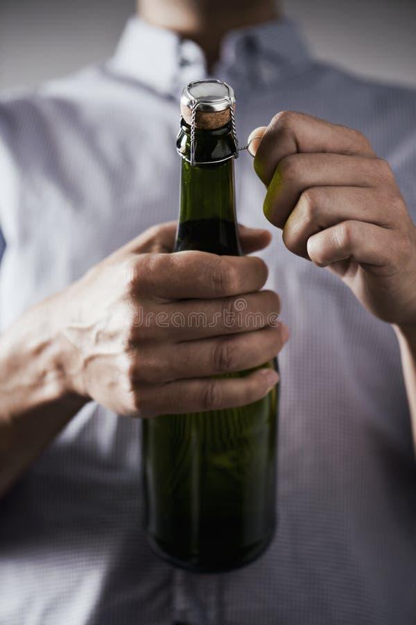 Ung man som öppnar en flaska av champagne arkivfoto
